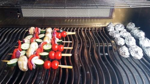 Gemüsespieße und Kartoffeln liegen auf.
