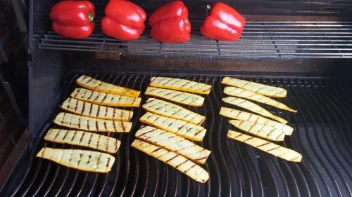 Marinierte Zucchini und Paprika werden für den Gemüsesalat gegrillt.
